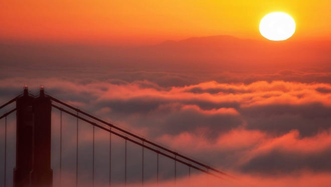 Golden sunrise: The sun peeks above the fog Tuesday morning near San Francisco's Golden Gate bridge. The photo was submitted to USA TODAY via Your Take at yourtake.usatoday.com
