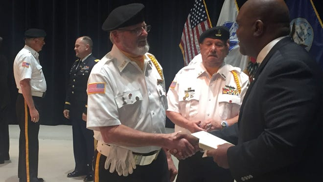 Vietnam War veterans Harold Burgess, 66, of New Baltimore, left, and Ron Graus, 68, of New Baltimore, shake hands and receive their pins from James Jackson, from Senator Gary Peters office on Oct. 21, 2016 in Warren.