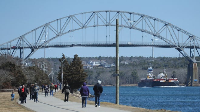 A barge heads under the Bourne Bridge as walkers take to the trail along the Cape Cod Canal.