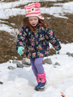 Giada Marshall, 4, of Webster runs along side her snow boat as it heads down the course.