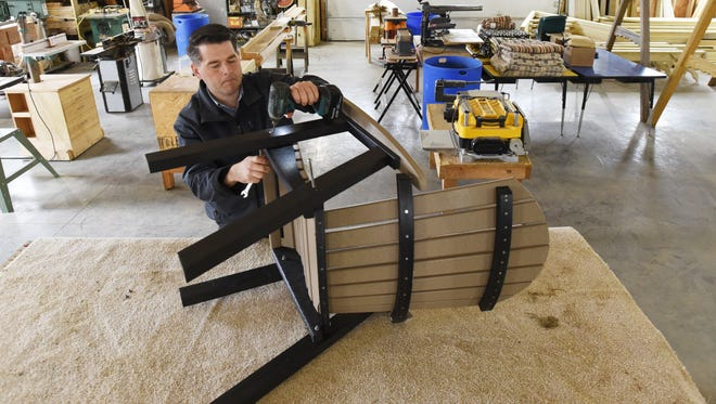 Owner Jesse Martin assembles a chair at Down Home Lawn Furniture near Zanesville recently.