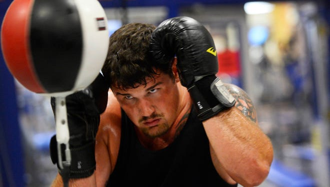Penn State defensive tackle Anthony Zettel works straight combinations with a double end bag during a workout with professional MMA and muay thai coach Bruce Lombard at Titan Fitness and Martial Arts in State College Wednesday, July 22, 2015. The workout starts with two punch combinations and works up to five.