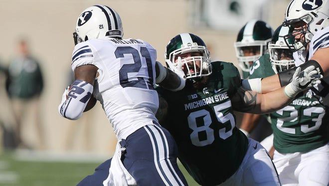 Michigan State Spartans Evan Jones tackles BYU Cougars Jamaal Williams.