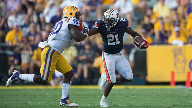 Auburn running back Kerryon Johnson (21) stiff arms LSU linebacker Devin White (40) as he pushes him out of bounds during the NCAA football game between Auburn and LSU on Saturday, Oct. 14, 2017, at Tiger Stadium in Baton Rouge, La. LSU defeated Auburn 27-23.