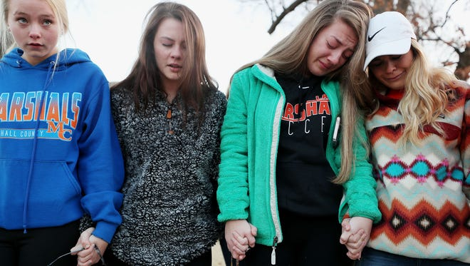 Students Brooklyn Boyce, left, and Katlyn Gamble cry as they hold hands with other Marshall County High School classmates during a prayer vigil for their classmates Wednesday, Jan. 24, morning outside at Paducah Tilghman High School. Two students were killed and 18 were injured Tuesday morning at Marshall County High School in Benton, Ky.