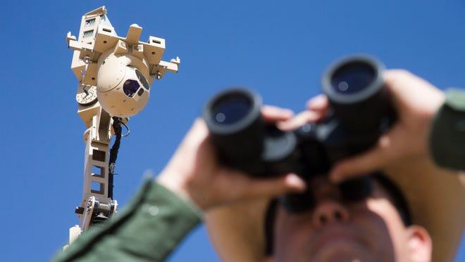 Border Patrol Agent Marcos Soto monitors a remote location at the border using high-tech security cameras and binoculars.