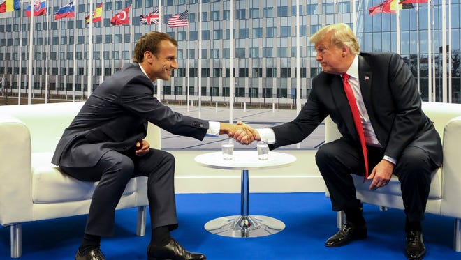 President Donald Trump shakes hands with French President Emmanuel Macron during a bilateral meeting at the NATO summit, in Brussels, Belgium.
