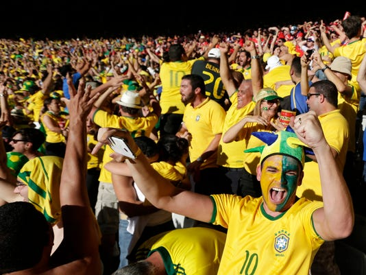 Brazil soccer fans celebrate their team's victory over Chile after a penalty shootout at a World Cup round of 16 match at Mineirao Stadium in Belo Horizonte, Brazil, Saturday, June 28, 2014. Brazil won 3-2 on penalties after the game ended 1-1. (AP Photo/Petr David Josek)
