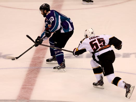 Cincinnati Cyclone Byron Froese (55) battles for control of the puck against Orlando Solar Bear Taylor Matson (10).