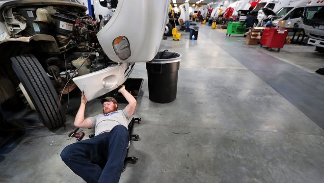 Mechanic Andrew Somes works on a delivery truck at the TAG service center which does everything from routine maintenance to catastrophic repair on some 500 trucks a month at the company's new site on American Way. TAG has merged with Lonestar Truck Group and created one of the nation's largest Daimler Truck dealerships.