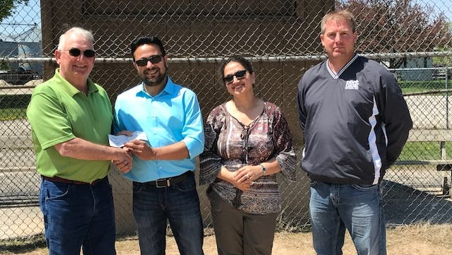 Town of Brussels Chairman Jim Wautier, left, accepts a check from Parvinder Jandu, Renuka Jandu and Joel Daoust, town supervisor.