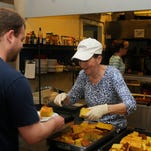 Lynn Calpin, center, of LaGrange, a volunteer at The Lunch Box, a soup kitchen in the City of Poughkeepsie, serves Erik Platania, left, of the City of Poughkeepsie.