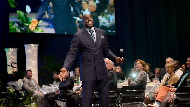 """Earvin """"Magic"""" Johnson steps down off the stage to speak to the hundreds at the Special Evening with Earvin """"Magic"""" Johnson event fundraiser for the Lansing Promise scholarship program Thursday night."""