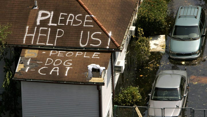 A plea for help appears on the roof of a home flooded