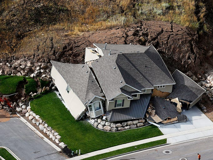 A home is destroyed following a landslide in a hillside community of North Salt Lake, Utah, Tuesday, Aug. 5, 2014. At least a dozen other homes have been evacuated.  (AP Photo/The Deseret News, Ravell Call)