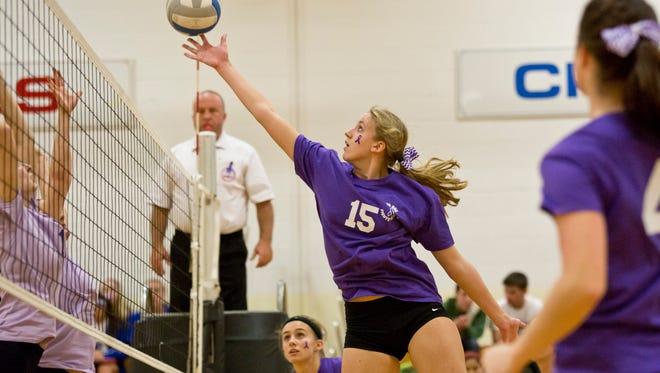Cardinal Mooney's Anna Vorderbrueggen tips the ball over the net during a volleyball game.