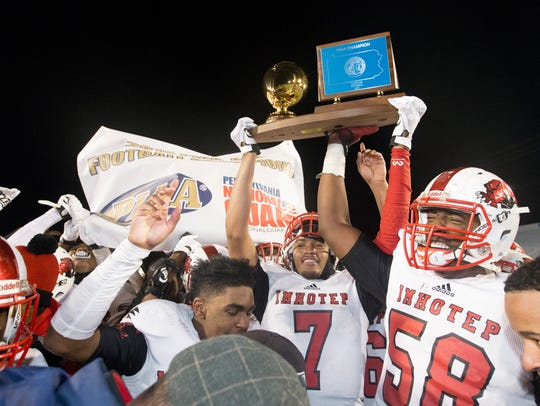 Imhotep Charter players, including Penn State's Shaka Toney (7) and Jahmir Johnson, right, celebrate with the state championship trophy after their 2015 PIAA Class AAA high school football championship game victory. (Charles Fox/The Philadelphia Inquirer via AP) ORG XMIT: PAPHQ324
