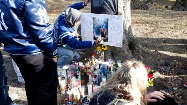 Friends and relatives on Saturday visit a memorial at the crash site where 18-year-old driver Joseph Touri was killed in Port Chester. His passenger, Diana Pineda, a 16-year-old Port Chester girl, remains hospitalized.