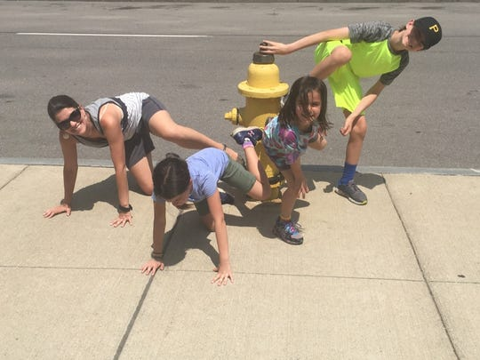 Jamie Buss finds a fire hydrant as part of an Operation City Quest challenge with her children (from left: Ella, 9, Lucy, 7, and Tyler, 13). You get additional points for submitting creative pictures.