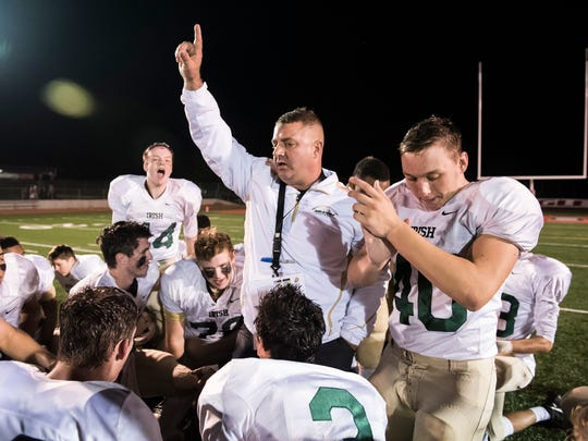 York Catholic head coach Eric Depew celebrates with his team after the Fighting Irish defeated Bermudian Springs 41-26 on Friday, Oct. 20, 2017.