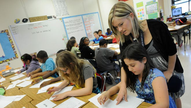 "Amy Lawson, a fifth-grade teacher at Silver Lake Elementary in Middletown, Del., helps student Melody Fritz with an English language arts lesson Oct. 1, 2013. The percentage of respondents in a Harris Poll who agreed with the statement ""students respect teachers"" dropped from 79% to 31%."