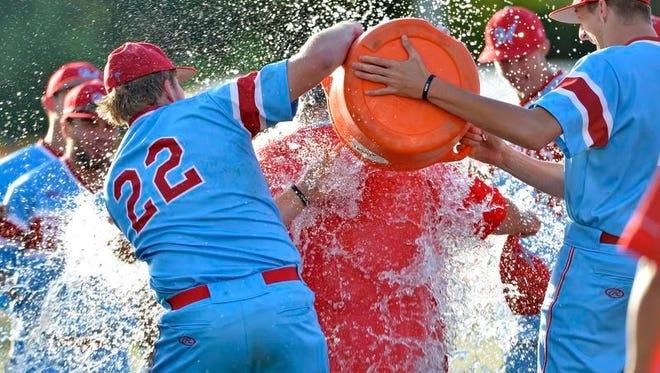 J.L. Mann baseball players douse Coach Brian Simpson in water after the Patriots won the Class AAAA Upper State championship Friday.
