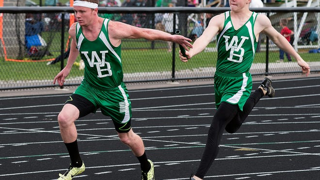 West Branch's Rob Lozier, left, receives the baton from teammate Cohen Lamp as they compete in the 4x100-meter relay.