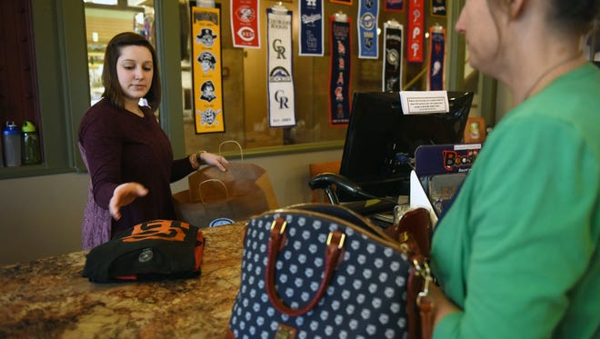Kathryn Macziewski, owner of A League of Your Own, checks out customer, Susan Simon, in the downtown Sioux Falls on Monday.