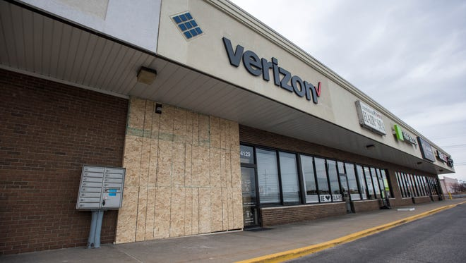 The damaged wall is boarded up Monday, April 3, after a vehicle crashed through the Fort Gratiot Verizon store.