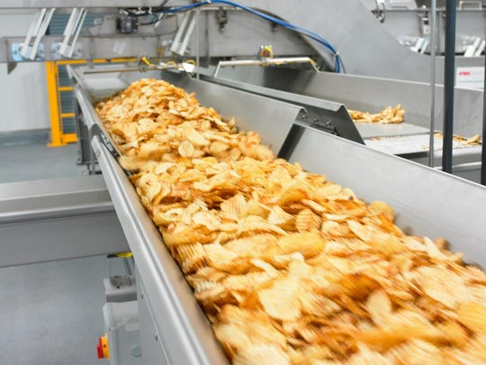 Krinkle-cut chips move on a conveyor after being fried at the Kettle Brand's plant in Salem.