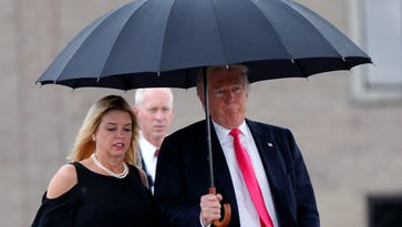 Republican presidential candidate Donald Trump walks in the rain with Florida Attorney General Pam Bondi as they arrive at a campaign rally in Tampa on Aug. 24, 2016.