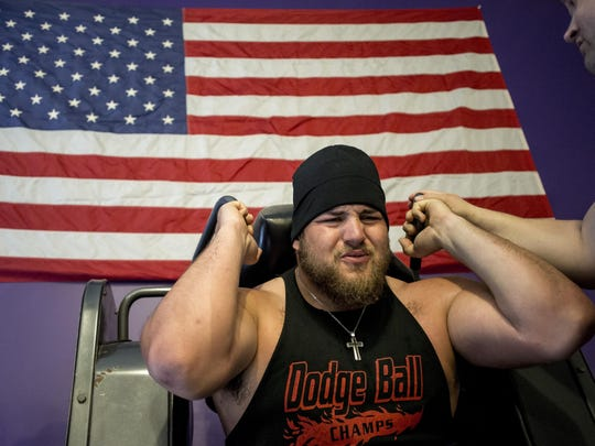 New Orleans Saints offensive lineman Tim Lelito cringes as he works out on a machine Wednesday, April 13, 2016 at No Bull Strength and Performance in Fowlerville.