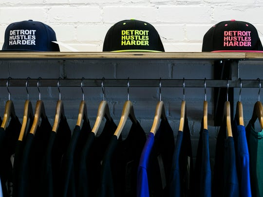 Flat bill hats sit and t-shirts sit on display at the
