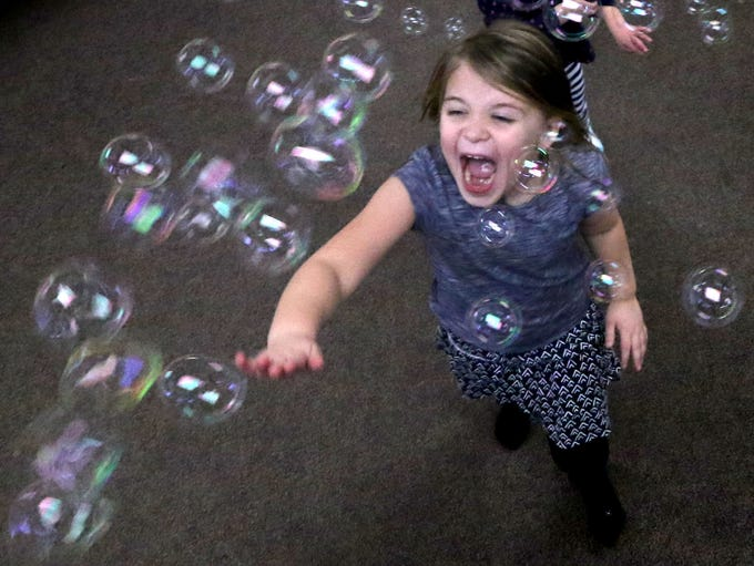 Meadow Mertes plays with bubbles emitting from a machine