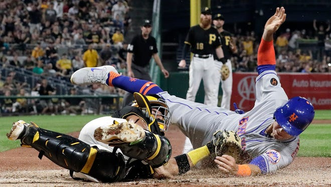 New York Mets' Michael Conforto, right, makes contact with home plate to score ahead of the tag by Pittsburgh Pirates catcher Elias Diaz during the sixth inning of a baseball game in Pittsburgh, Friday, July 27, 2018. Conforto tagged up at third on a line out to left by Jose Reyes.