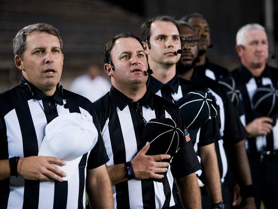 The officiating crew stands during the national anthem