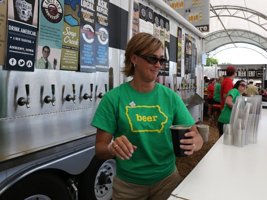 Cortney Thede of Waukee pours a glass of porter at the Iowa Craft Beer tent during the Iowa State Fair on Thursday, Aug. 14, 2014, in Des Moines.