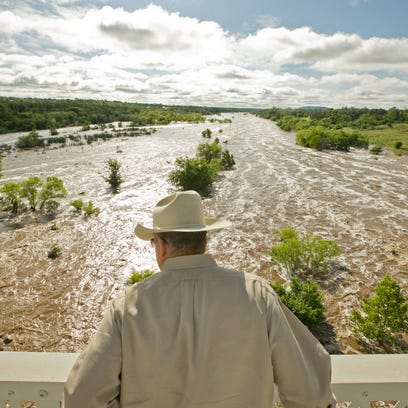 Tex Toler watches the Llano River rise after heavy rains in Llano, Texas.