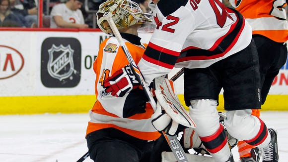 New Jersey Devils' John Quenneville, right, collides
