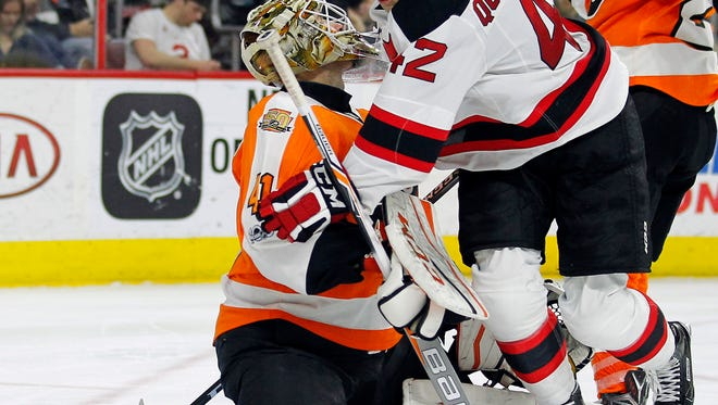 New Jersey Devils' John Quenneville, right, collides with Philadelphia Flyers goalie Anthony Stolarz during the third period of an NHL hockey game, Saturday, April 1, 2017, in Philadelphia. The goal Quenneville made was challenged and resulted in the play being ruled off-side. The Flyers won 3-0. (AP Photo/Tom Mihalek)