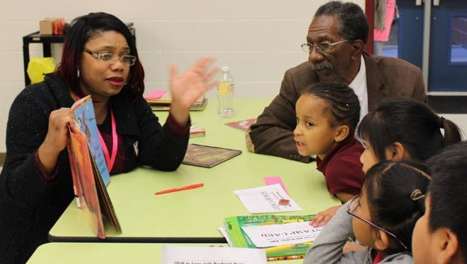 """Nicole Wright reads to guests during """"Fall in Love with Reading, Family Reading Night"""" at Quarter Mile Lane School in Bridgeton."""