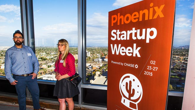 Ray Cabrera, streetscape programs manager for Downtown Phoenix, Inc. (left) chats with Sara Anderson, downtown Phoenix events manager for Downtown Phoenix, Inc., before the start of Phoenix Startup Week on the 19th floor of One 11 Tower in downtown Phoenix, Monday, Feb. 23, 2015.