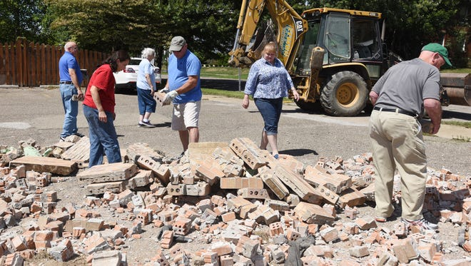 A backhoe leaves the scene Tuesday after dumping a fresh load of bricks in the parking lot at the corner of Forest and Laurel avenues in Zanesville. The bricks were from the former Good Samaritan Hospital and are available for anyone who wants to get a memento from the facility.