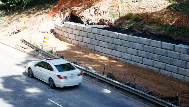 Asheville's Hendersonville Road sidewalk project is progressing using various approaches to obstacles, including cutting away at banks and building retaining walls. Planners expect to return to the council to ask for an additional $300,000.