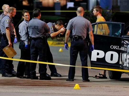 Oklahoma City police take photos of Christian Costello, son of Oklahoma Labor Commissioner Mark Costello, before placing him in a police vehicle, Sunday, Aug. 23, 2015, at the scene where Mark Costello was fatally stabbed in Oklahoma City. Christian Costello was arrested on a first-degree murder complaint, police said.