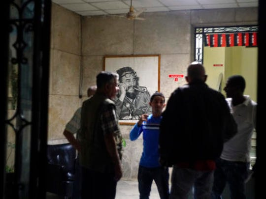 People gather at an office of the Popular Assembly decorated with a picture of Cuban leader Fidel Castro in Havana, Cuba, early Saturday November 26, 2016. Former President Fidel Castro, who led a rebel army to improbable victory in Cuba, embraced Soviet-style communism and defied the power of 10 U.S. presidents during his half century rule, has died at age 90.