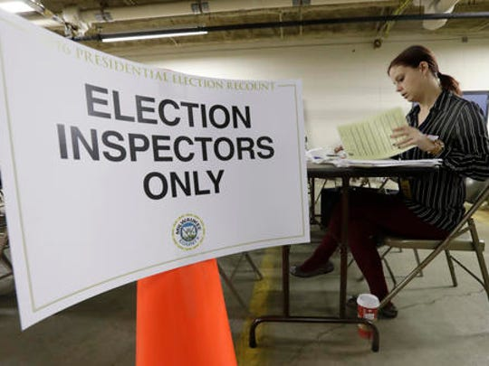 Nicole Kirby looks over results during a statewide presidential election recount Thursday, Dec. 1, 2016, in Milwaukee. The first candidate-driven statewide recount of a presidential election in 16 years began Thursday in Wisconsin, a state that Donald Trump won by less than a percentage point over Hillary Clinton after polls long predicted a Clinton victory.
