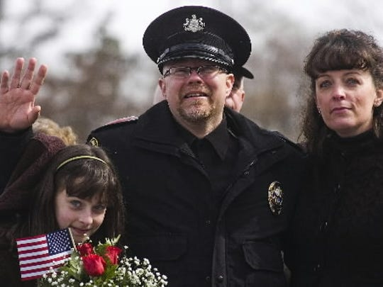 Former Eastern Adams Regional Police officer Rick Phillips waves to a crowd of supporters alongside his step-daughter, Brianna Milliken, then 12, left, and wife April, after arriving at the York Airport in Feb. 2011 from a rehabilitation center in North Carolina.