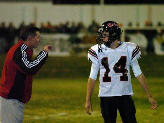 Maryville coach George Quarles talks to quarterback Derek Hunt between plays in a game in 2005.