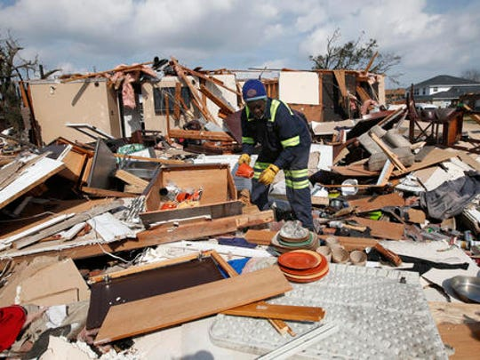 Willie Anderson tries to salvage possessions from his daughter's destroyed home, in the aftermath of Tuesday's tornado that tore through the New Orleans East section of New Orleans, Wednesday, Feb. 8, 2017.  Officials say tornadoes that struck in southeastern Louisiana destroyed homes and businesses, flipped vehicles and left thousands without power.